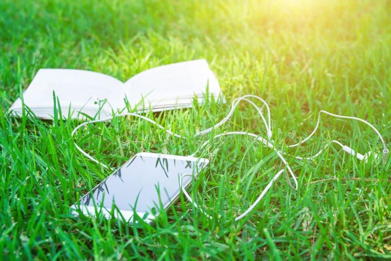 Раскройте книгу и белый Smartphone при наушники лежа на зеленой траве в парке на яркий солнечный весенний день лета Образование стоковые изображения rf