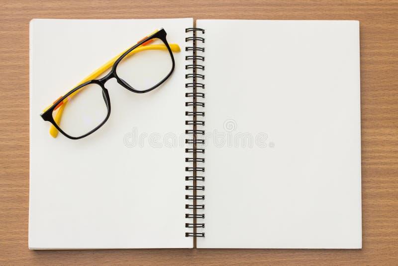 Раскройте книгу и стекла на деревянной предпосылке стоковая фотография rf