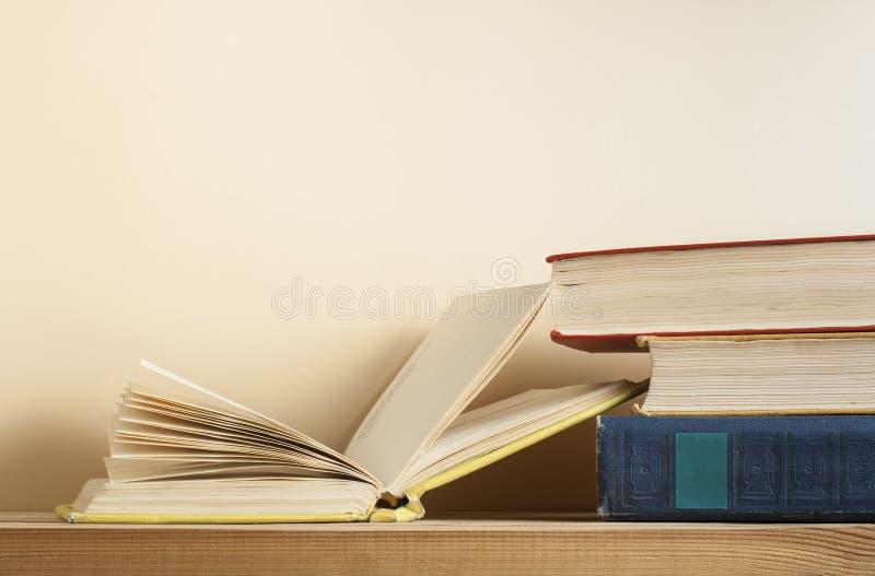 Раскройте книгу и стог книг на деревянном столе Предпосылка образования задняя школа к Скопируйте космос для текста стоковое фото