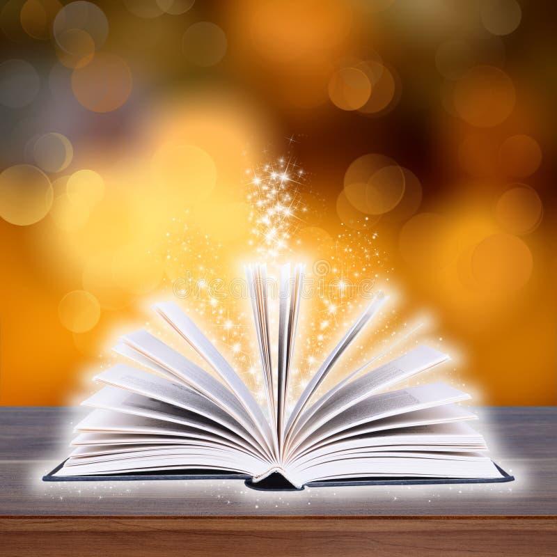 Раскройте книгу с светом bokeh на деревянных планках стоковые фотографии rf