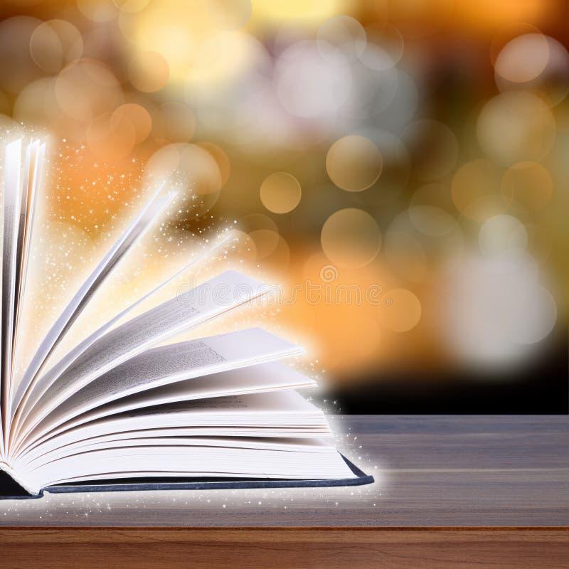 Раскройте книгу с светом bokeh на деревянных планках стоковые фото