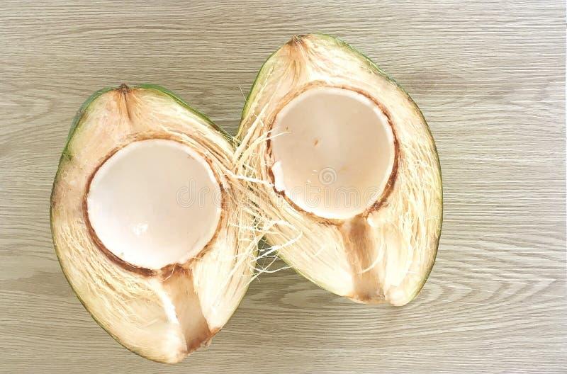Раскройте кокос на естественной выдержанной деревянной предпосылке стоковые изображения