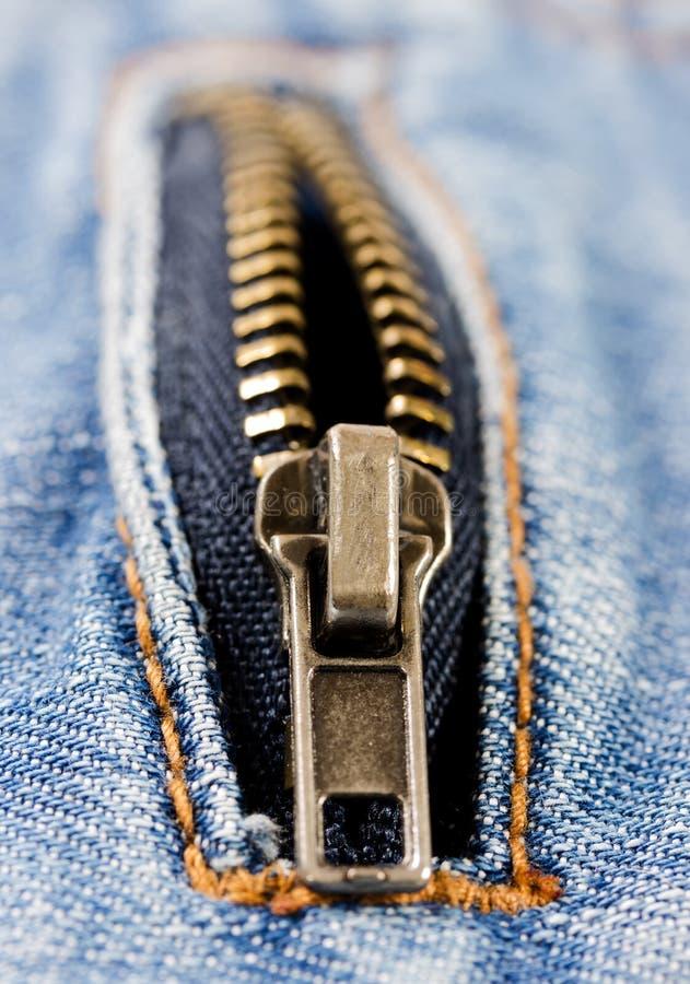 Раскройте молнию металла на предпосылке джинсовой ткани стоковая фотография