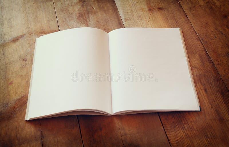 Раскройте пустую тетрадь над деревянным столом подготавливайте для модель-макета ретро фильтрованное изображение стоковые фотографии rf