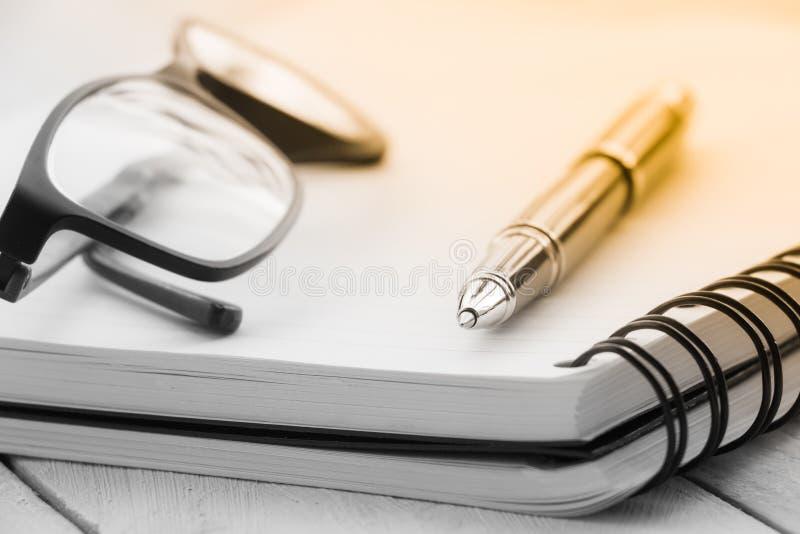 Раскройте пустую тетрадь, eyeglass ручки на предпосылке стоковые фотографии rf