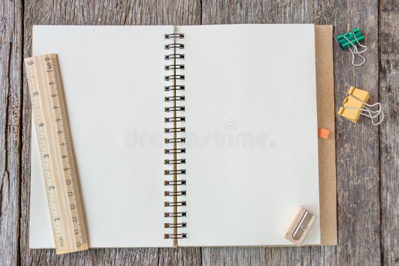 Раскройте тетрадь на деревянной предпосылке с деревянным правителем стоковое фото rf