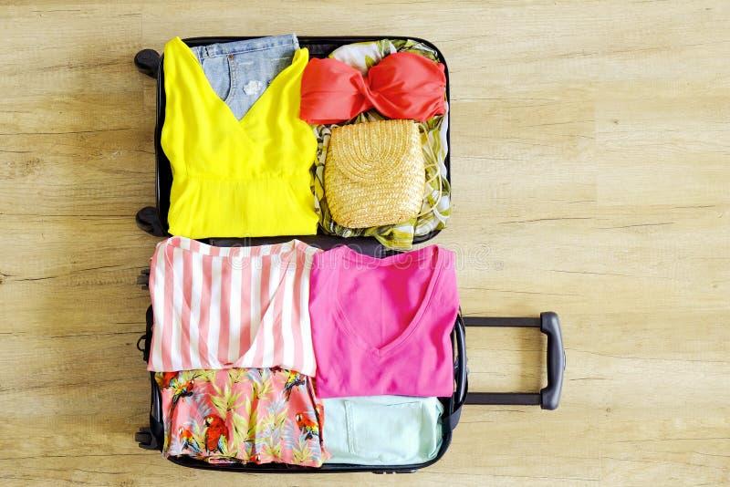 Раскройте чемодан полно упакованный с сложенными одеждой и аксессуарами ` s женщин на поле Упаковка женщины для тропической конце стоковые изображения rf