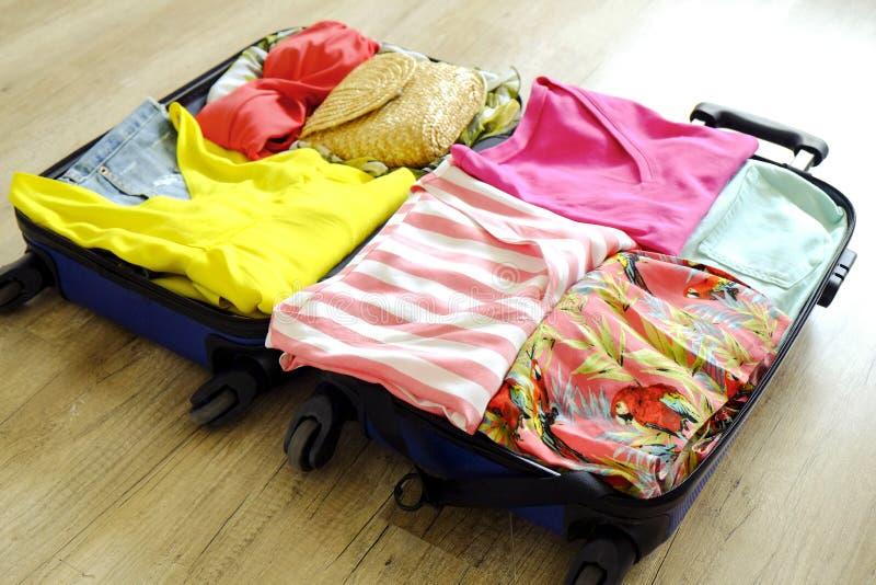 Раскройте чемодан полно упакованный с сложенными одеждой и аксессуарами ` s женщин на поле Упаковка женщины для тропической конце стоковое изображение rf