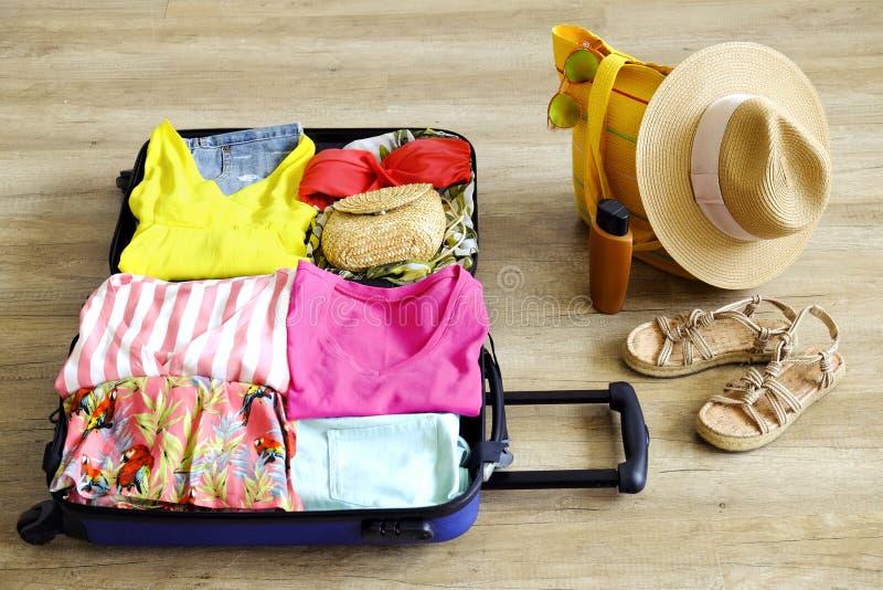 Раскройте чемодан полно упакованный с сложенными одеждой и аксессуарами ` s женщин на поле Упаковка женщины для тропической конце стоковое изображение