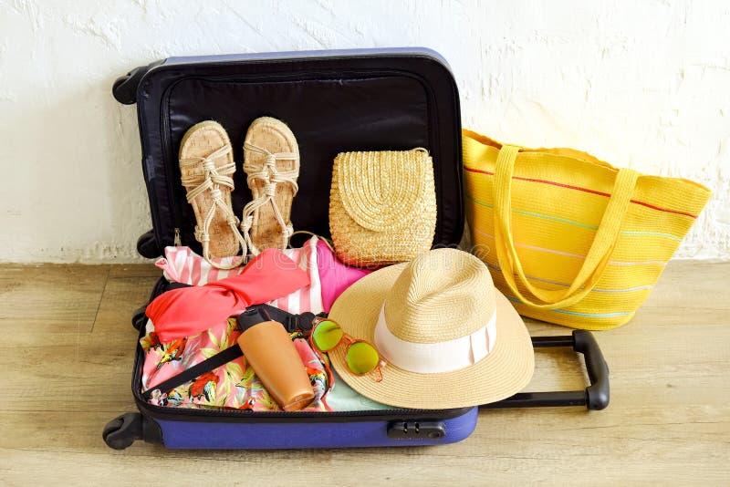 Раскройте чемодан полно упакованный с сложенными одеждой и аксессуарами ` s женщин на поле Упаковка женщины для тропической конце стоковое фото