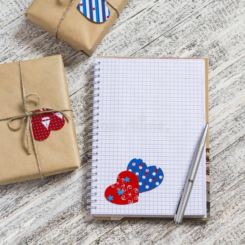 Раскройте чистый блокнот, домодельные подарки в бумаге kraft, бумажные сердца дня валентинки на белом деревянном столе стоковые фото