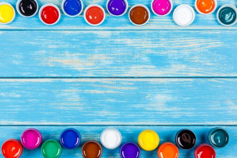 Раскройте чонсервные банкы краски с крышками на голубой деревянной предпосылке стоковое изображение rf