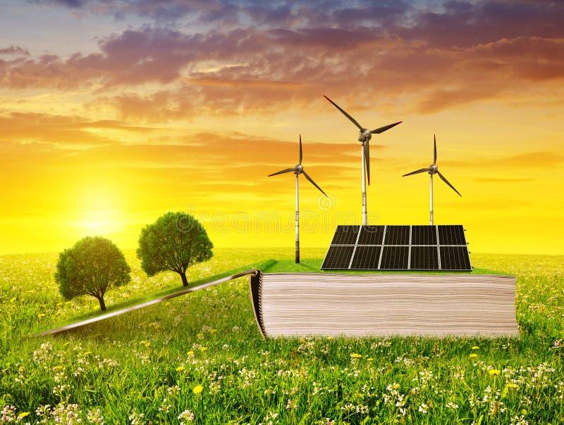 Раскройте экологическую книгу с панелью солнечных батарей и ветротурбиной на луге на заходе солнца стоковые изображения