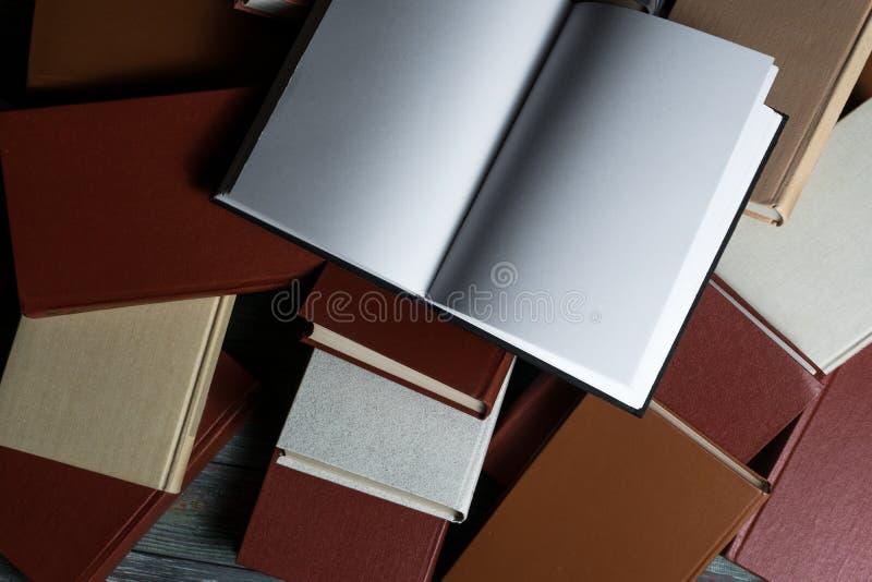 Раскройте hardback книги на книгах стога на деревянной предпосылке стоковое фото