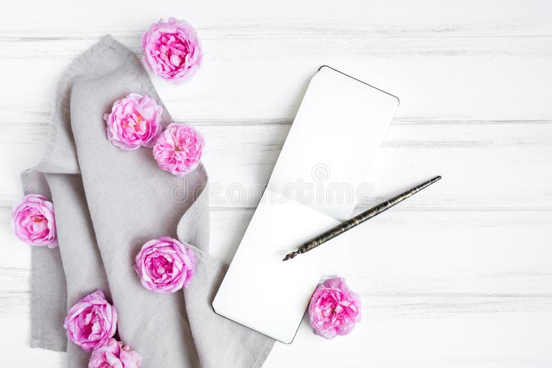 Раскройте sketchbook, красивые розовые розы на серой linen скатерти ткани Состав на белом винтажном деревянном столе Плоское поло стоковая фотография rf