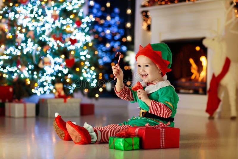 Раскрывать ребенка присутствующий на рождественской елке дома Ребенк в костюме эльфа с подарками и игрушками Xmas  стоковая фотография