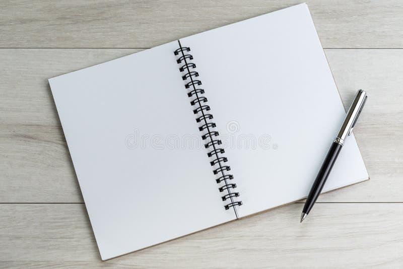 Раскрывая белые пустые бумага и ручка примечания на свете - сером деревянном tabl стоковое изображение