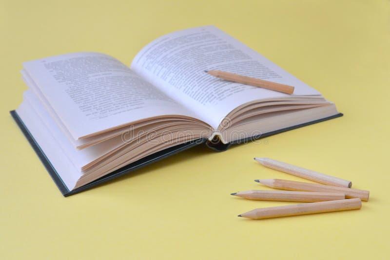 Раскрытая книга и деревянные карандаши на желтой предпосылке с космосом экземпляра стоковое фото
