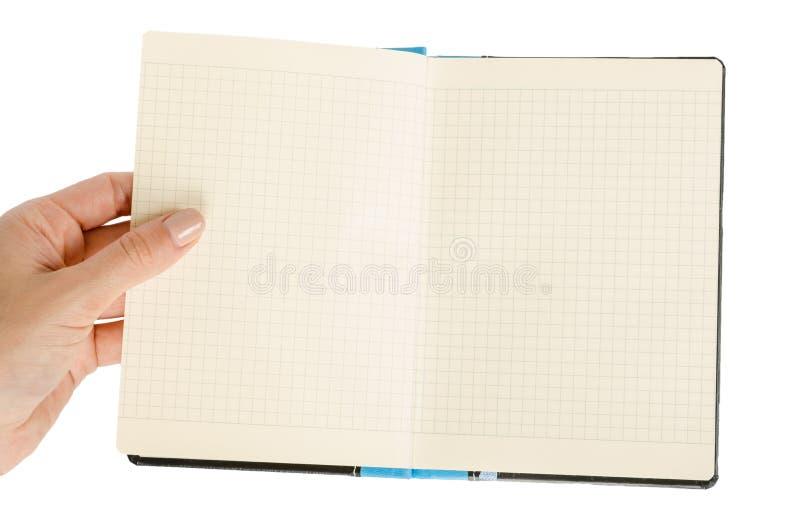Раскрытая черная тетрадь при рука, изолированная на белой предпосылке стоковое изображение rf