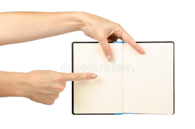Раскрытая черная тетрадь при рука, изолированная на белой предпосылке стоковые фото