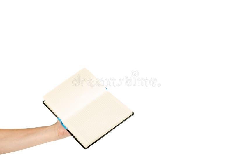 Раскрытая черная тетрадь при рука, изолированная на белой предпосылке, шаблон космоса экземпляра стоковое фото
