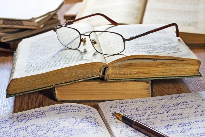 Раскрытые тетрадь, пер, книги и стекла стоковая фотография rf