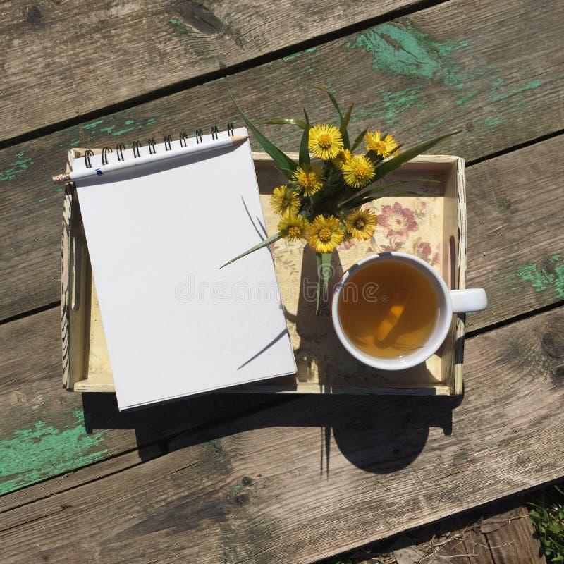 Раскрытый блокнот, чашка чаю и малый букет полевых цветков на подносе на старой деревянной предпосылке стоковая фотография rf
