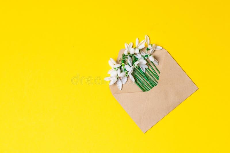 Раскрытый конверт бумаги ремесла вполне цветков цветения весны на белой предпосылке Взгляд сверху стоковые изображения rf
