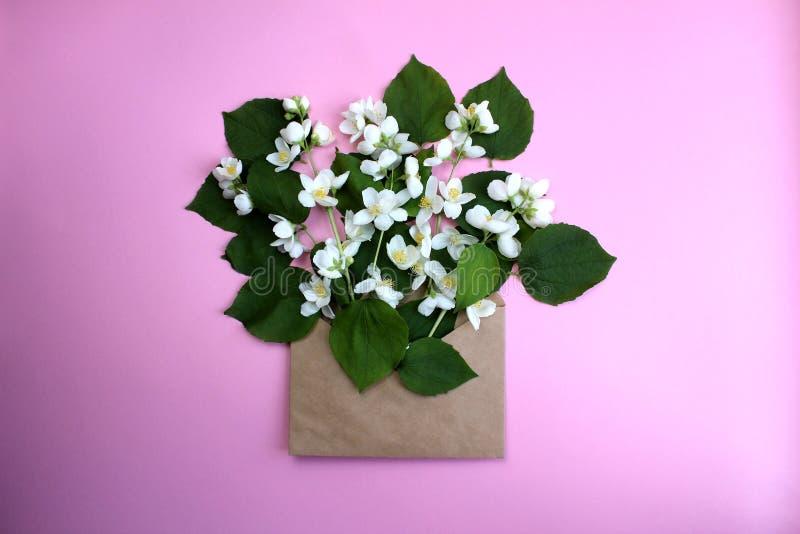Раскрытый конверт с расположениями цветков на розовой предпосылке, взгляде сверху Праздничная приветствуя концепция стоковая фотография rf