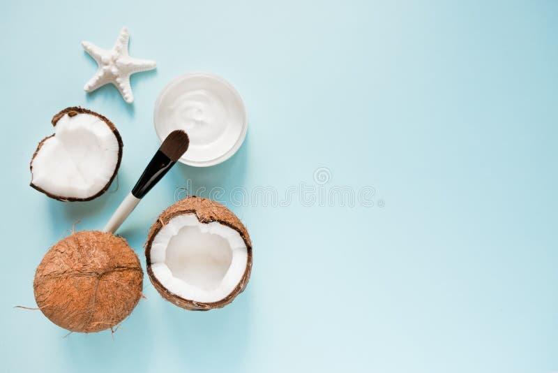 Раскрытый стеклянный опарник со свежим кокосовым маслом и зрелыми кокосами на голубой предпосылке Органическая здоровая концепция стоковые фотографии rf