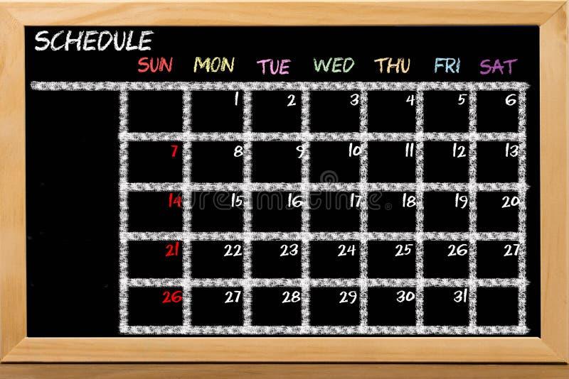 Расписание с расписанием решетки на черной предпосылке доски стоковые изображения