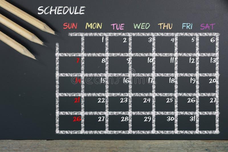 Расписание с расписанием решетки на черной предпосылке доски стоковая фотография rf