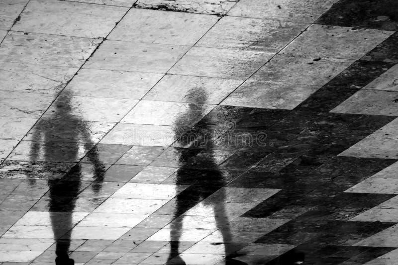 Расплывчатый силуэт отражения 2 людей идя совместно в t стоковые фото