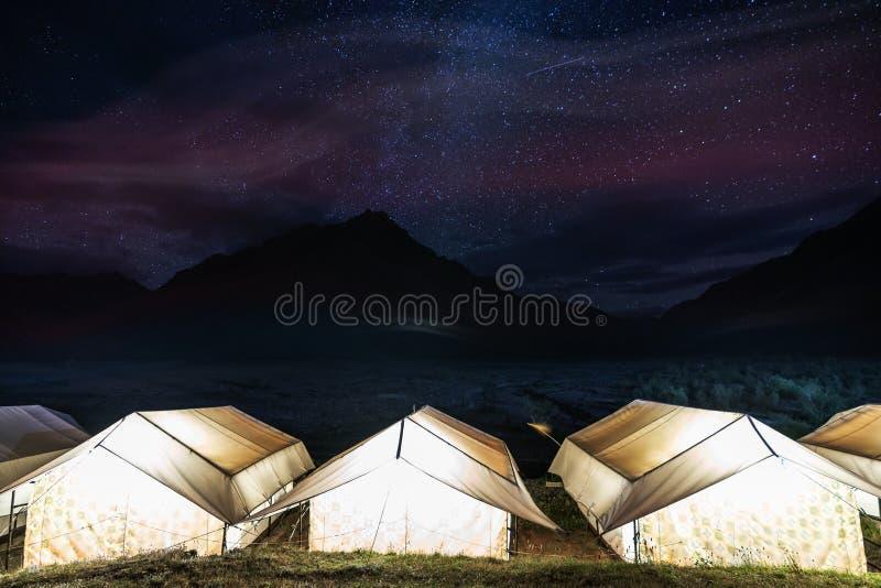 Располагаться лагерем под красочным небом вполне звезд Накаляя шатры с горами и небом силуэта вполне звезды на монастыре Rangdum  стоковая фотография
