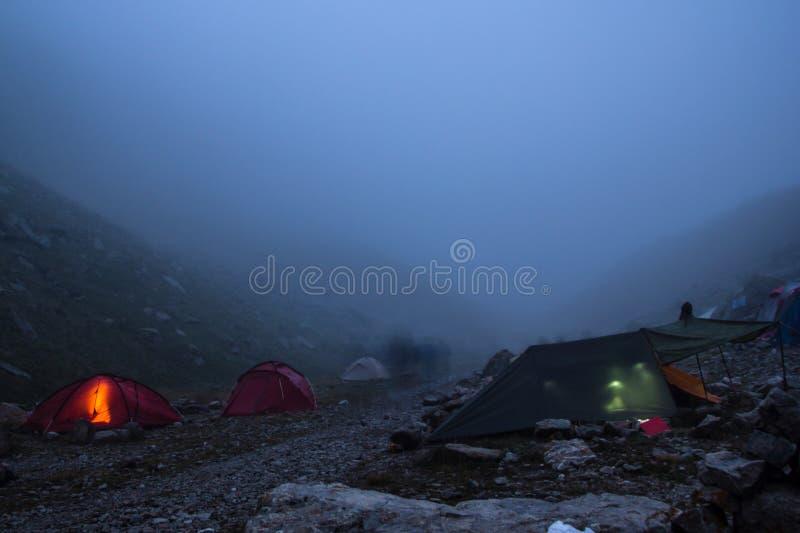 располагающся лагерем с шатрами и туристами в долине горы на ноче и тумане, русских стоковые изображения rf