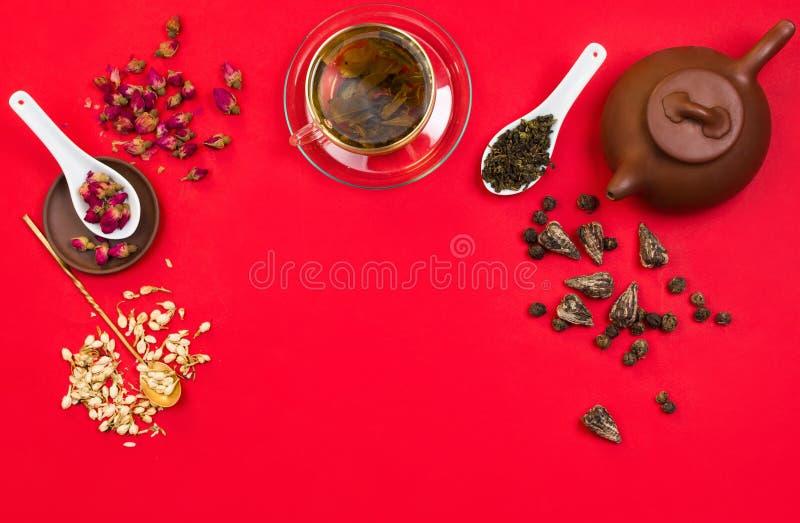 Расположение рамки Flatlay с китайским зеленым чаем, розовыми бутонами, цветками жасмина и сухими листьями чая стоковые изображения