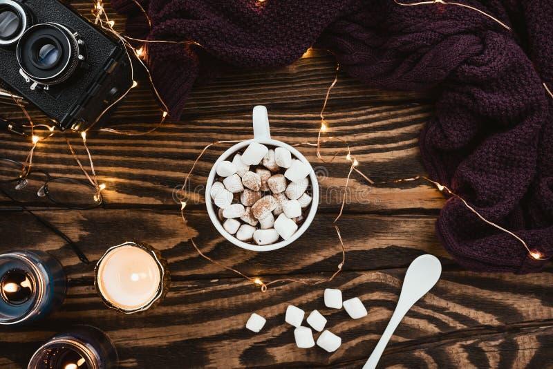 Расположение уютной зимы flatlay со светами рождества, какао vegan, стеклами, связанным свитером и свечами стоковые изображения rf