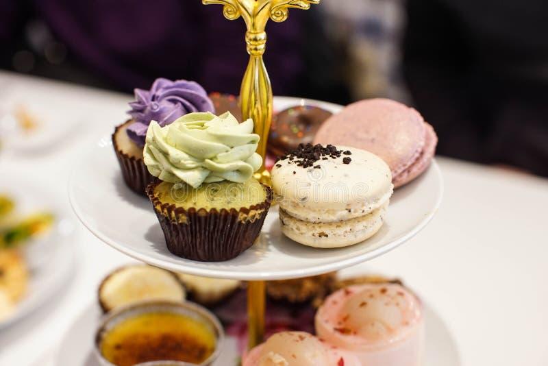 Расположенная ярусами стойка с разнообразие укусом определила размер десерты стоковое фото