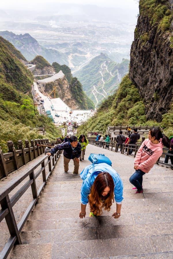 Расположенные ярусами туристы взбираясь 999 лестниц к воротам гавани в горах Tianman стоковое фото rf