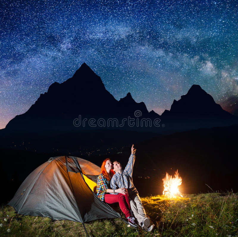 Располагаться лагерем ночи Счастливые туристы пар сидя около шатра и огня и наслаждаясь неимоверно красивым звёздным небом, млечн стоковая фотография