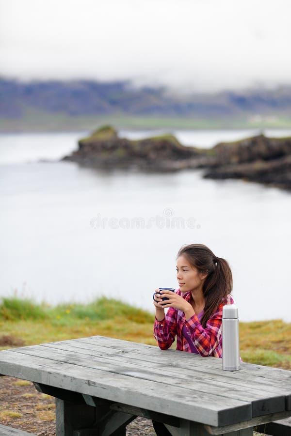 Располагаясь лагерем женщина сидя на кофе таблицы выпивая стоковое фото