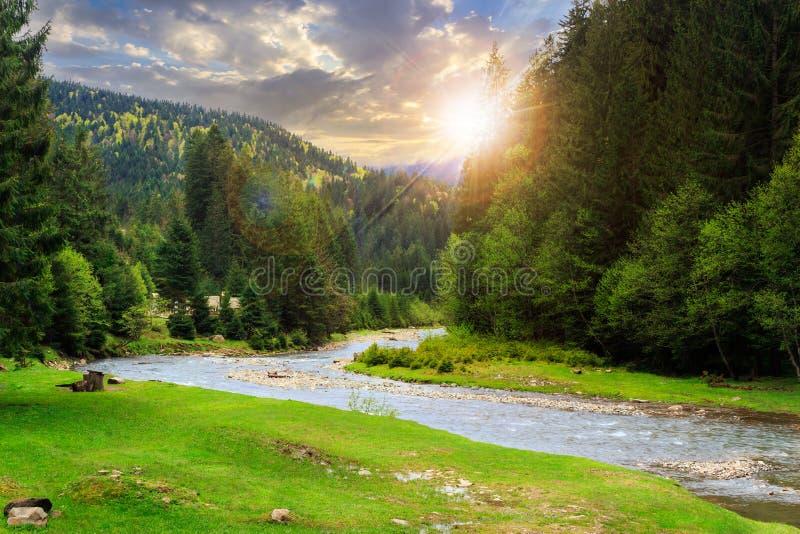 Располагаясь лагерем место около реки горы на заходе солнца стоковое изображение rf