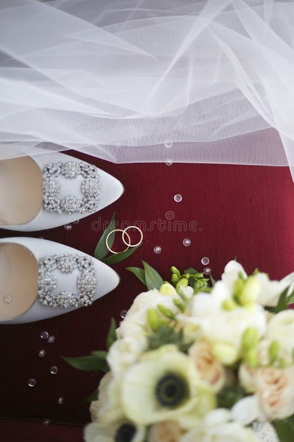 Расположение свадьбы, кольца, ботинки, вуали и bridal букет стоковое фото