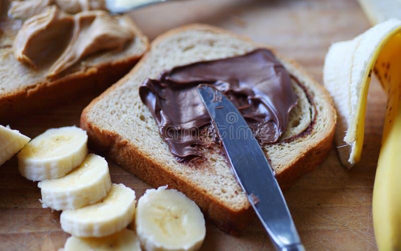 Распространение шоколада, арахисовое масло и сандвич банана стоковое фото rf