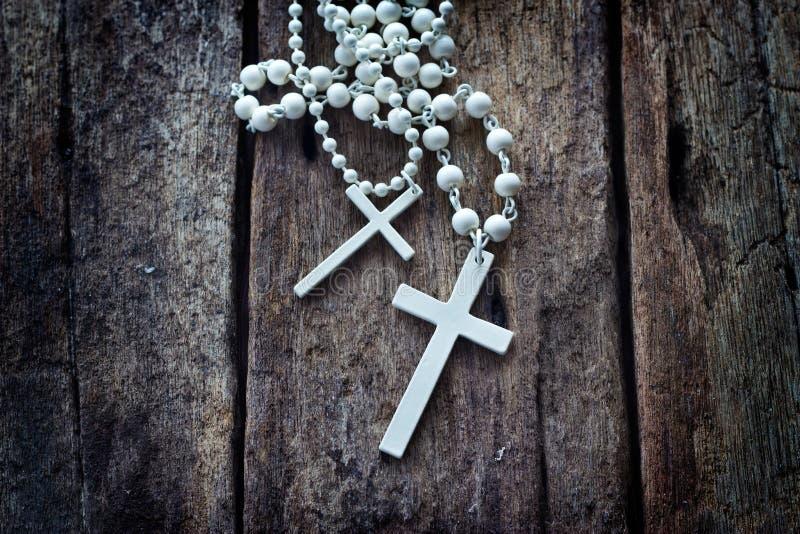 Распятие ожерелья белое на старом деревянном столе стоковая фотография