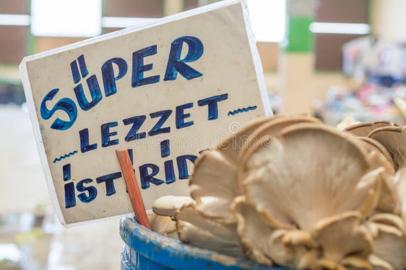 Расплывчатые свежие грибы устрицы с супер устрицей вкуса маркируют позади на счетчике в типичном базаре greengrocery в Турции стоковая фотография