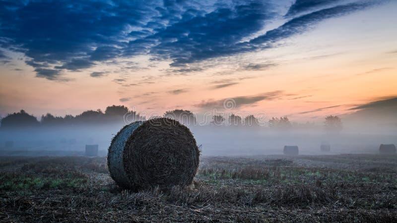 Рассветайте на туманной долине в осени с сеном на поле стоковая фотография