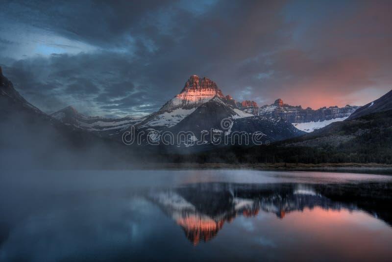 Рассвет озера Swiftcurrent туманный, национальный парк ледника, Монтана, США стоковые изображения rf