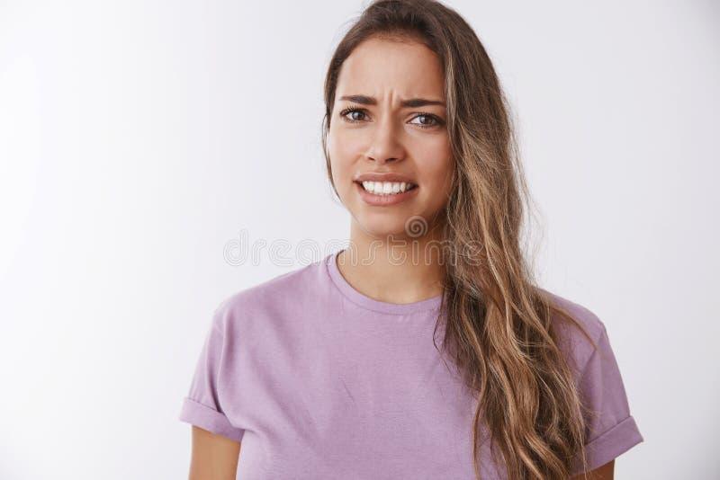 Рассказ слуха женщины портрета привлекательный неудовлетворенный гримасничая опостылеть хмурясь обхватывающ зубы отвращение, неже стоковое изображение rf