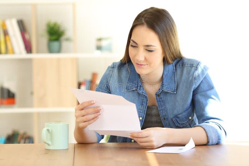 Расслабленная дама читая письмо дома стоковые фото